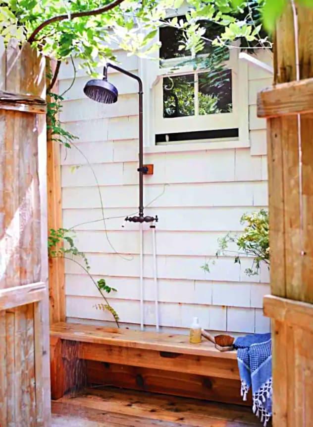 Idea para ducha exterior anexa a casa, con banco de madera para disfrutar